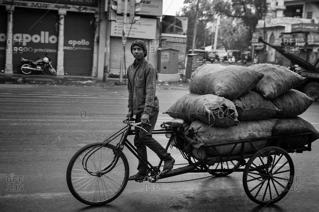 Jaipur, India - March 1, 2015: Man pedaling a bicycle cart loaded with bags on a street in Jaipur, India