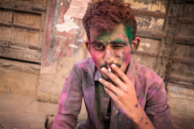 Pushkar, India - March 6, 2015: Man covered in dye smoking a cigarette during the Holi Festival in Pushkar, India