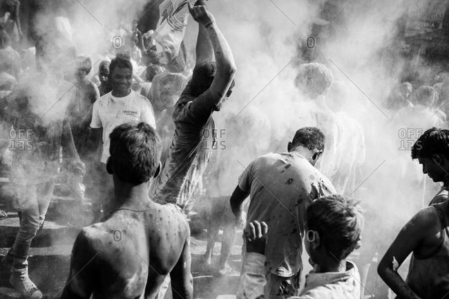 Pushkar, India - March 6, 2015: Men standing in clouds of dye during Holi Festival in Pushkar, India