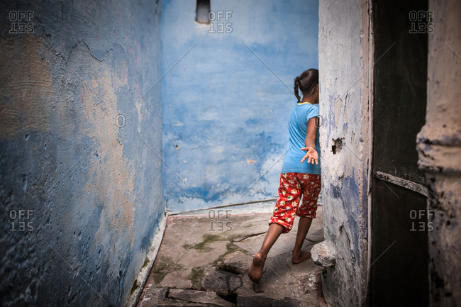 Girl running around the corner of an alley in Udaipur, India