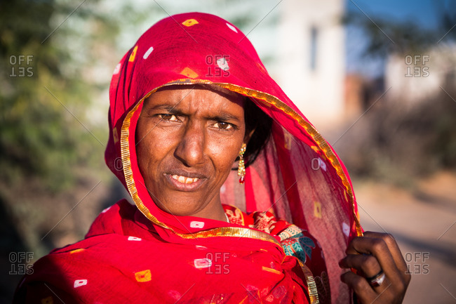 Rajasthan, India - March 16, 2015: Portrait of an Indian woman in a red sari and head scarf