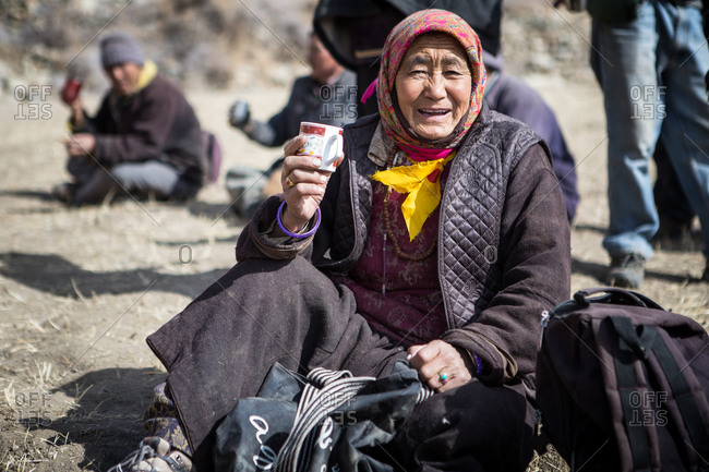 Leh Ladakh, India - February 11, 2015: Woman sitting outside with other villagers in the Himalayan region of Leh Ladakh, India