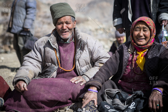 Leh Ladakh, India - February 11, 2015: Couple sitting outside with other villagers in the Himalayan region of Leh Ladakh, India