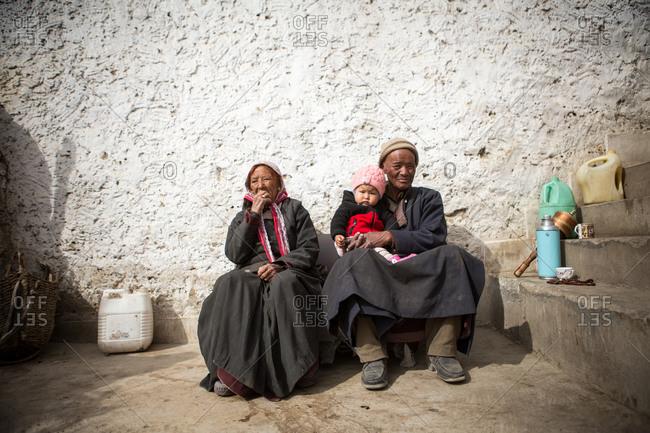 Leh Ladakh, India - February 11, 2015: Couple sitting outside with a child in the Himalayan region of Leh Ladakh, India