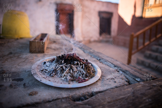 Smoke rising from a plate of incense outside in the Himalayan region of Leh Ladakh, India