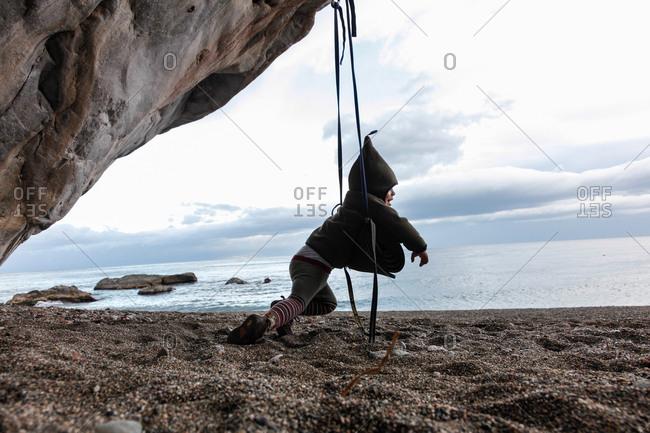 Boy 2 years swinging at beach, Taormina, Messina, Sicily, Italy
