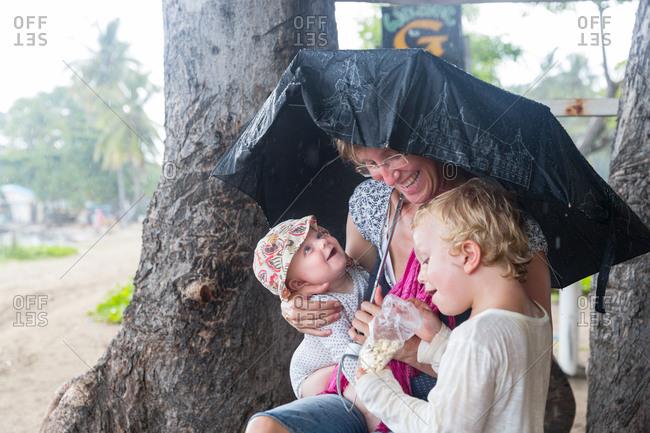 Mother with her two children under umbrella