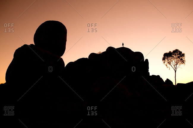 Silhouette of a person standing on top of Devils Marbles rock formation
