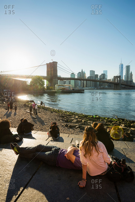Tourist and locals on rocks of Fulton Ferry State Park in Dumbo