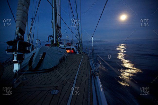 Sailing boat, yacht with night lighting system and full moon during Atlantic crossing, Sailing