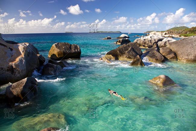 Woman snorkeling in the rock formation The Baths on Virgin Gorda, British Virgin Islands, Caribbean Sea