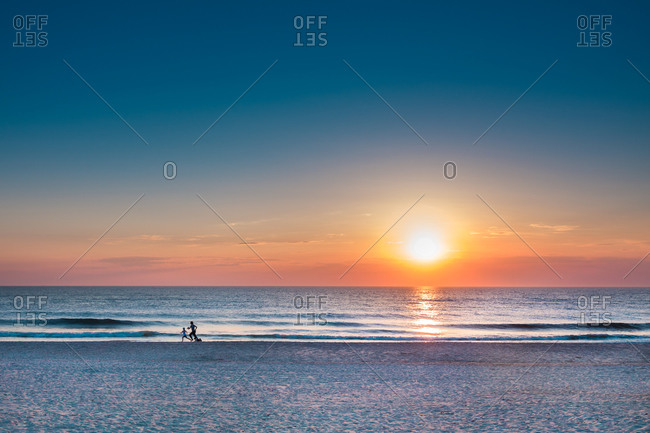 Runners on beach during sunset, Sylt Island, North Frisian Islands, Schleswig-Holstein, Germany