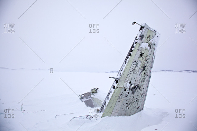 Parts of a crashed airplane in the snow-covered tundra