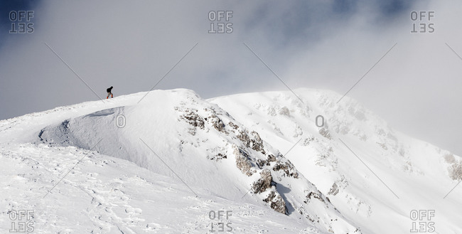 Hiker climbing on a snowy peak, ascend to Unnutz Mountain