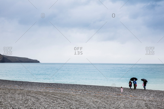 A family on the pebble beach of Birdlings Flat at Banks Peninsula