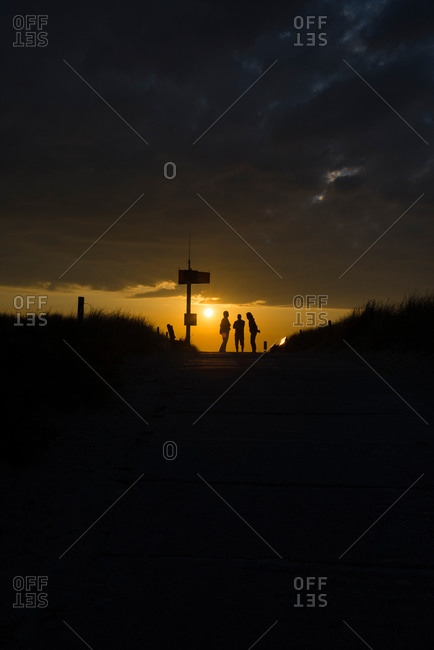 Three people standing at the entrance to the beach against the light of sunset