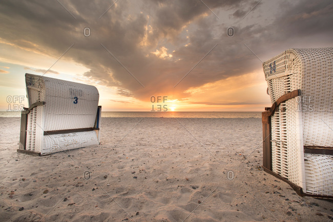 Beach chairs on the beach in Dierhagen in front of a cloudy sky and sunset