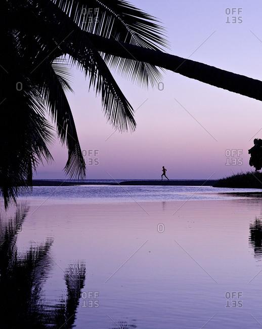 Man running along beach in sunset
