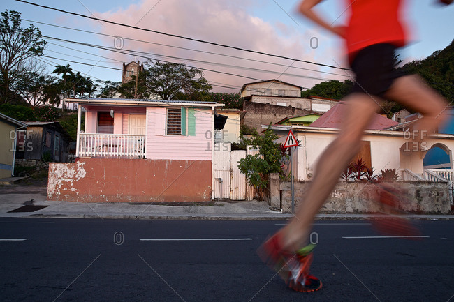 Young man running along a residential street