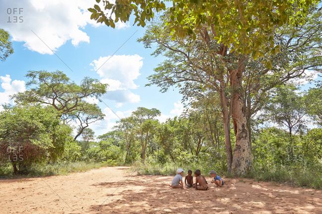 Boys on safari playing with kids from San bushman tribe