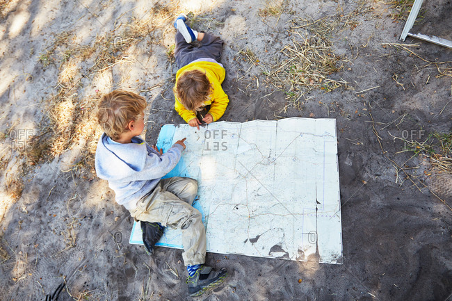Boys looking at a map in the sand