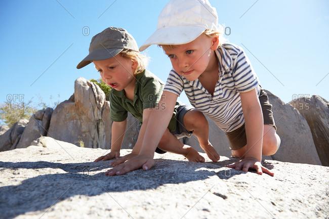 Two boys climbing over rocks, Kubu Island, Makgadikgadi Pans National Park