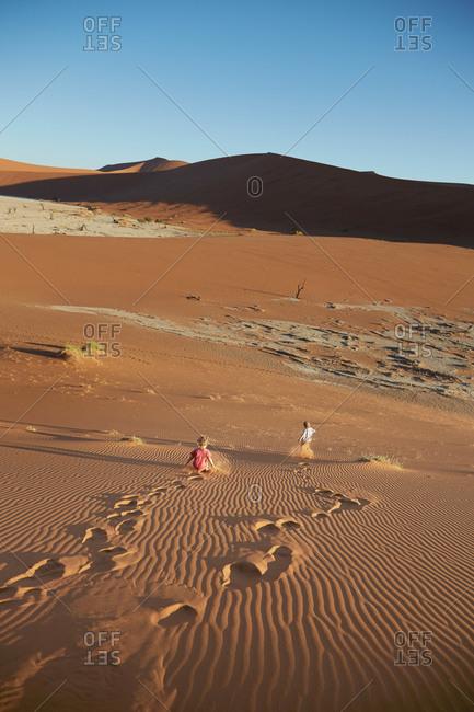 Two boys running down a sand dune, Dead Vlei, Sossusvlei, Namib National Naukluft Park