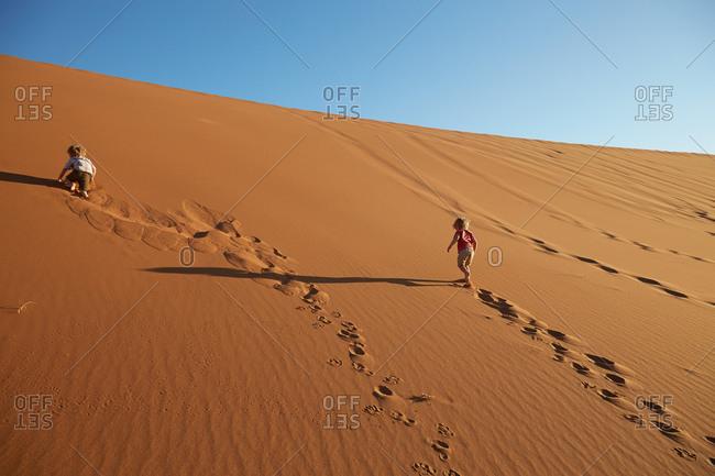 Two boys walking up a sand dune, Dead Vlei, Sossusvlei, Namib National Naukluft Park