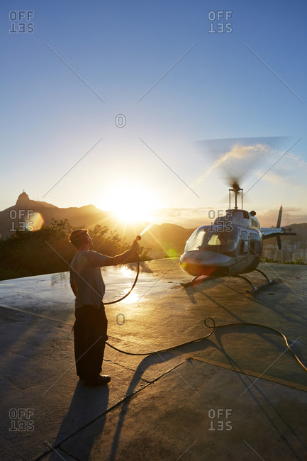 Helicopter rotors being cleaned with fresh water after helicopter flight