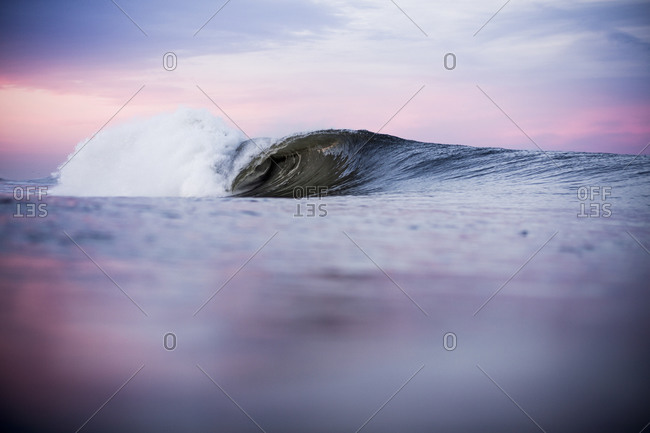 Waterline view of curling wave at sunset