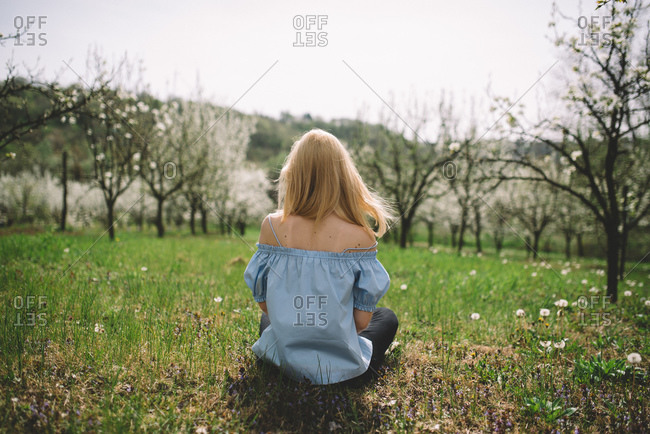 Back view of a woman sitting in a blossoming orchard