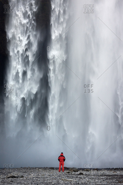Man standing beneath an imposing waterfall in Iceland