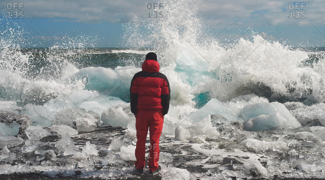 Man facing crashing waves on a frozen Icelandic beach