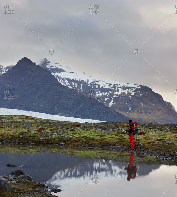 Man hiking along a glacial lake in Iceland