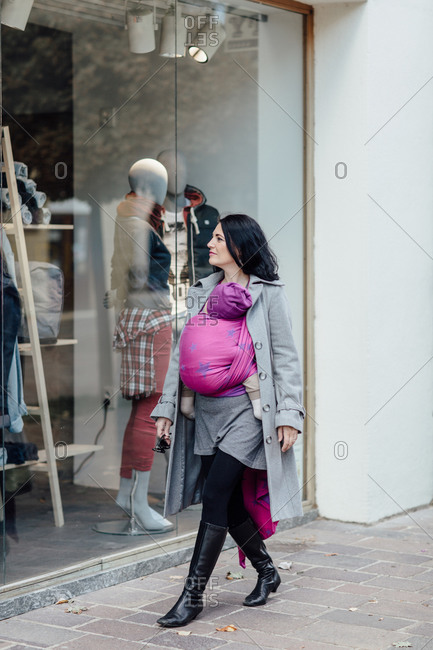 Mother carrying her child while window shopping