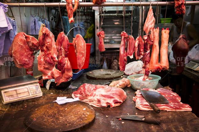 Hong Kong, China - September 15, 2015: Meat hanging in a butcher stall at Fa Yuen market in Hong Kong, China