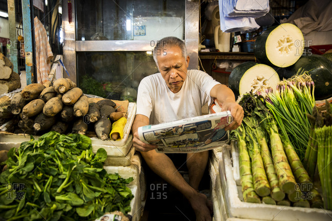 Hong Kong, China - September 15, 2015: Vendor reading a newspaper between his produce display at Fa Yuen market in Hong Kong, China