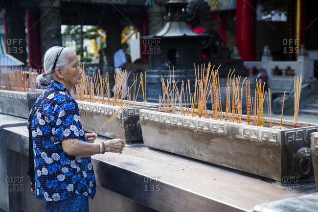Hong Kong, China - September 15, 2015: Woman burning incense at Sik Sik Yuen Wong Tai Sin Temple in Hong Kong, China