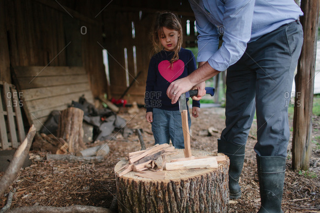 Father teaching daughter how to split firewood