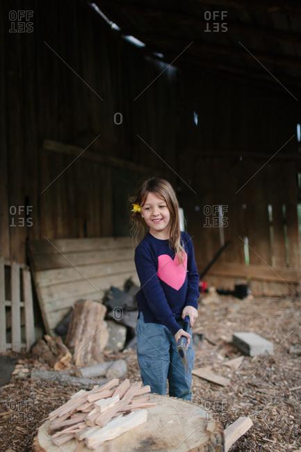 Little girl chopping firewood with an axe
