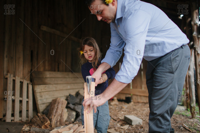 Man teaching girl how to split firewood with yellow flowers in their hair