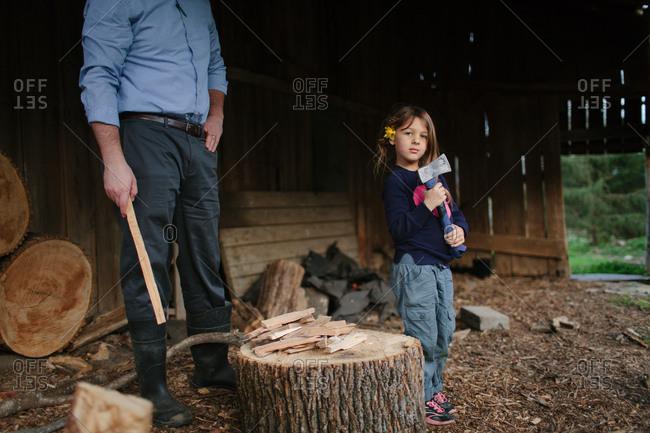 Little girl holding axe after chopping firewood