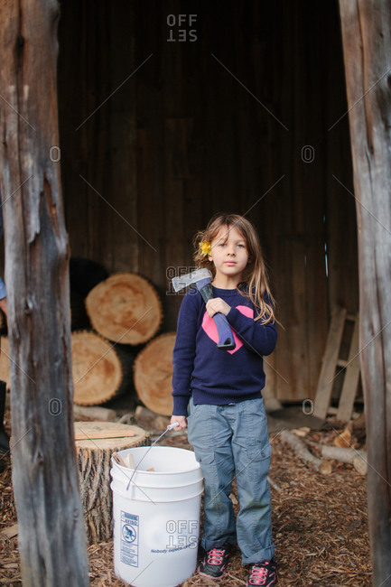 Little girl carrying bucket of firewood and holding an axe