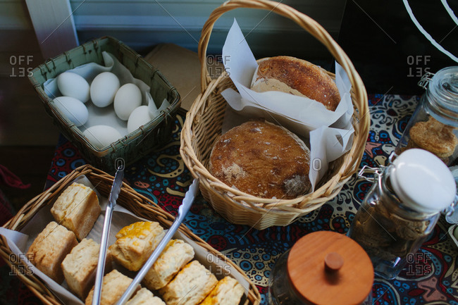 Bread, pastries and eggs in baskets on a colorful tablecloth