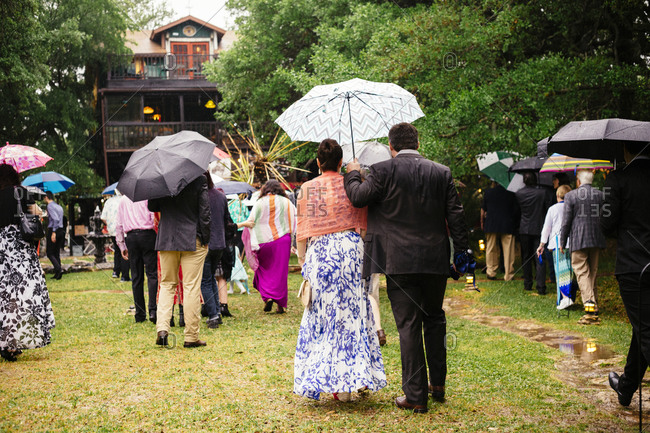 Group of people carrying umbrellas walking toward a house in the rain