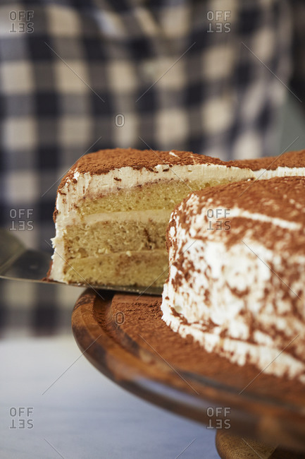 Close up of a person taking a slice of Tiramisu from a cake plate