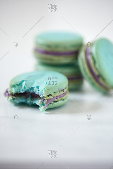 Close up of a stack of macaroons next to one with a bite taken from it