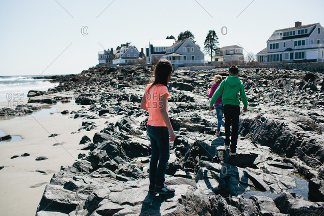 Three girls walking along a rocky beach at low tide
