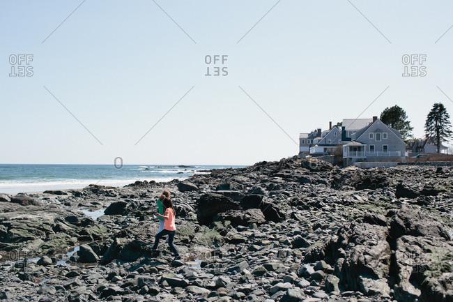 Two girls walking along a rocky beach at low tide