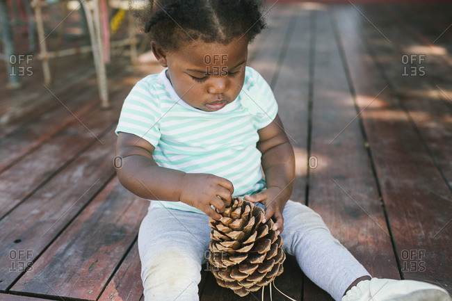 Baby girl sitting on deck playing with a pinecone